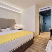 Habitación King con camas King size en tonos blancos y grises, azul y amarillo pie de cama
