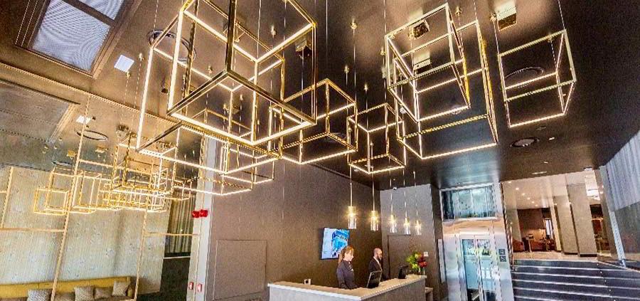 Recepción del hotel con lámpara cúbica de luz led. Destacan los tonos grises