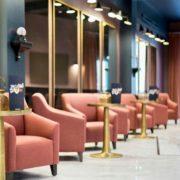 Zona de estar, bar de tonos azulados y comodas butacas naranjas
