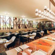 Vista del restaurante con mesas y sillas de distintos estilos
