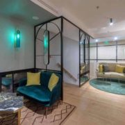 Descansillo zona de estar con distintos sofás y alfombras